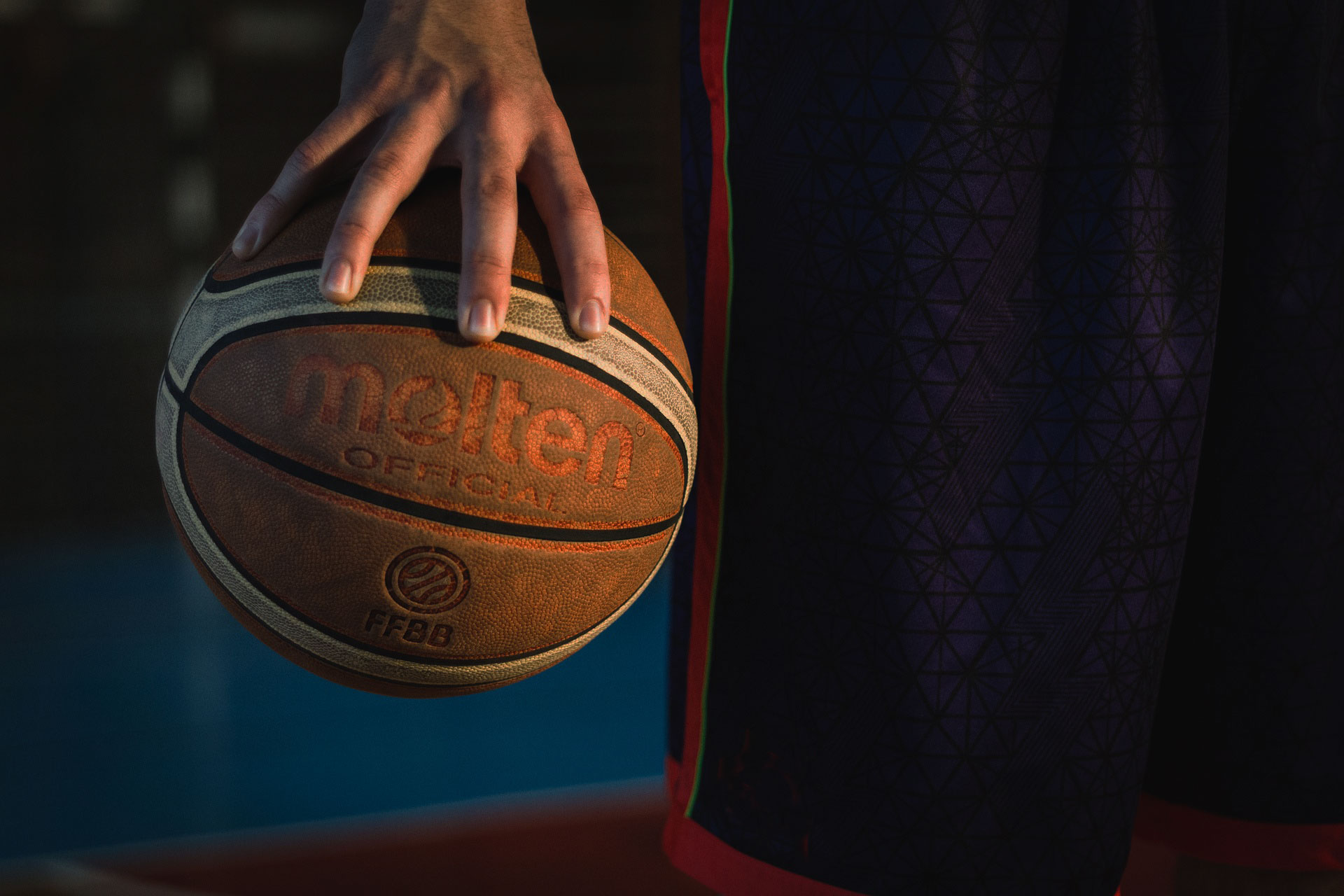 Mano che regge una palla da basket